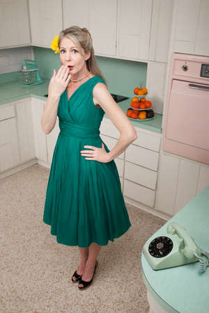 Forgetful middle-aged Caucasian woman with hand on hip in retro-styled kitchen scene photo