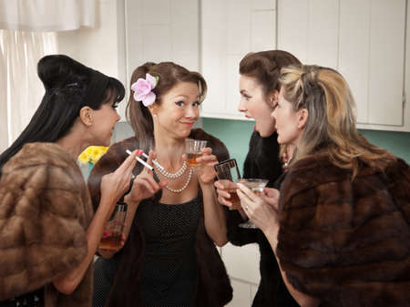 Four Caucasian women in mink coats smoking and drinking