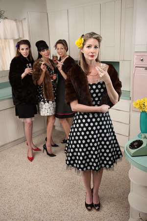 Four women smoking and drinking in a retro-style kitchen scene Фото со стока