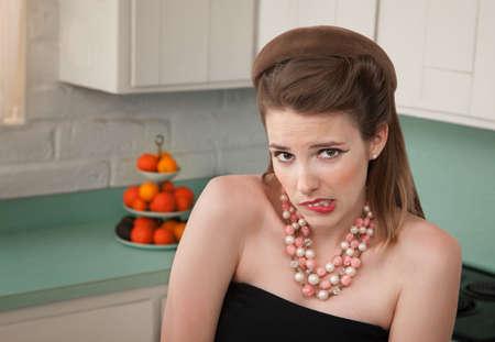 femme inqui�te: Inquiet de femme dans une cuisine mord sa l�vre