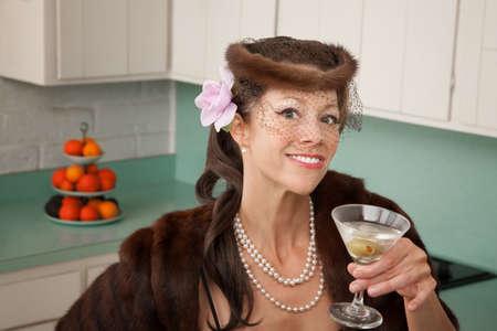 Caucasian woman wearing veil and mink coat enjoying martini in kitchen