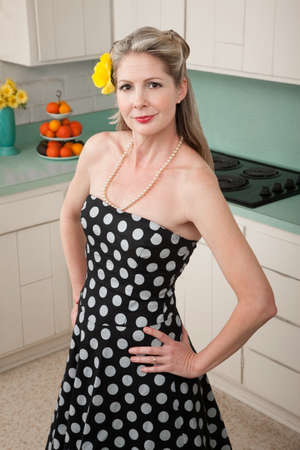Confident Caucasian woman with hand on hips in kitchen