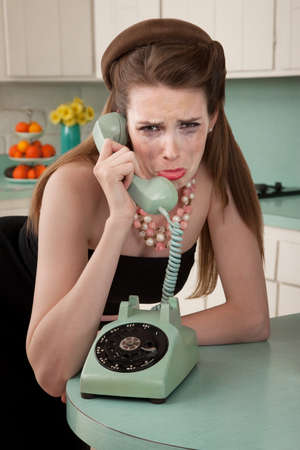 over the counter: Mascara smeared housewife crys on phone in a retro-style scene