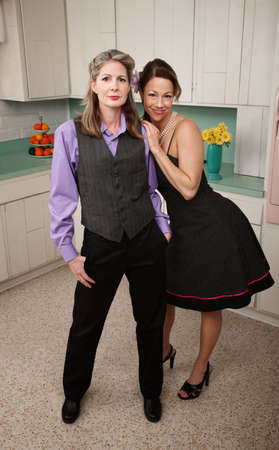 retro woman: Two happy women standing together in kitchen