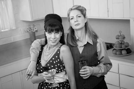 Lesbian couple with drinks and cigar in a retro-style kitchen photo