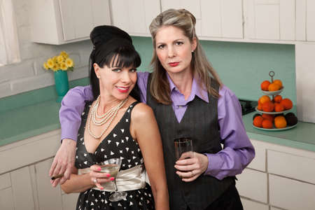 Two middle-aged Caucasian women drink in a retro-style kitchen
