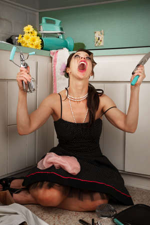 Woman screaming in frustration holding hand-blender and masher in kitchen photo