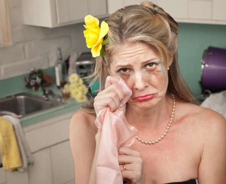 slob: Caucasian housewife wipes tears with napkin in her kitchen Stock Photo