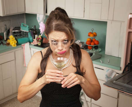 messy kitchen: Weeping Caucasian woman drinks a martini in her messy kitchen