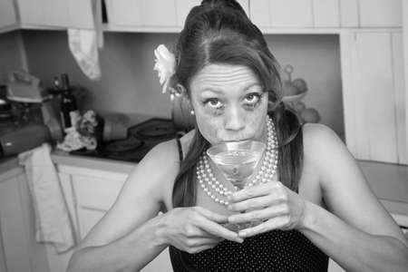 Drunk weeping Caucasian woman in a retro-style kitchen sips a martini  photo