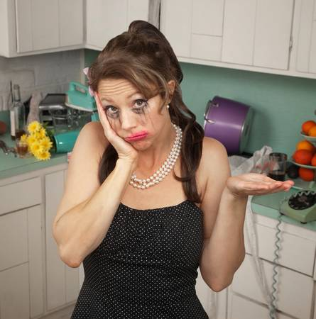 Unhappy weeping woman with hand on face in a kitchen photo