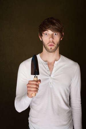 Shocked Caucasian man holding trowel on brown background photo