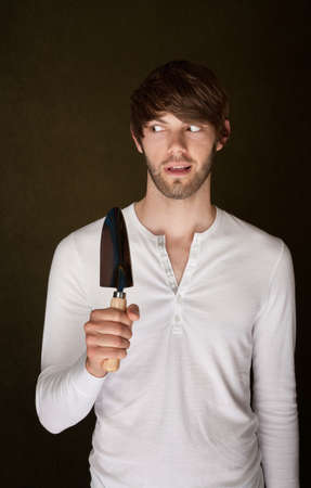 sneaky: Sneaky handsome Caucasian man with a garden trowel Stock Photo