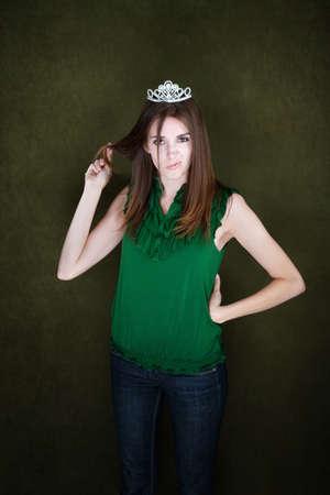 Bored young woman wearing a tiara twirls her hair 免版税图像