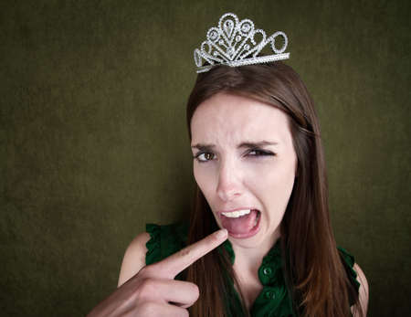 yuck: Disgusted Young Woman with a crown tiara and gagging gesture