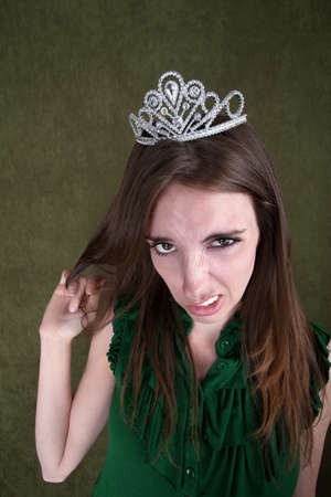 sneer: Caucasian woman with tiara plays with her hair Stock Photo