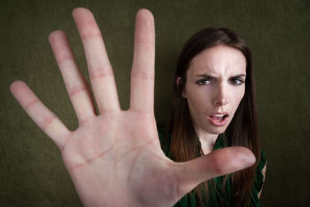 Pretty Caucasian woman gestures to stop with hand