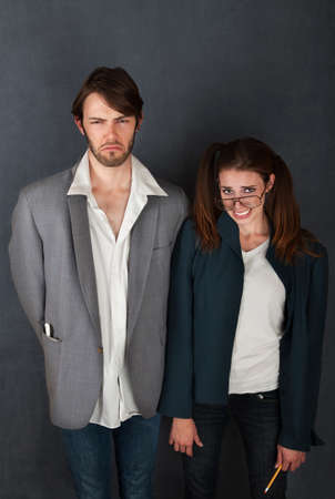 uncomfortable: Uncomfortable nerd man and woman couple on gray background Stock Photo