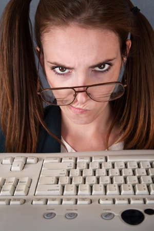 whiff: Serious female nerd in front of keyboard with drooping glasses