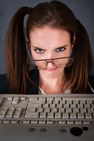 whiff: Upset female nerd in front of keyboard with drooping glasses