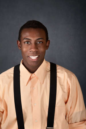 Cute young African-American adult with suspenders smiles Stockfoto