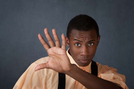 avoid: Young handsome Black male raises hand to block something
