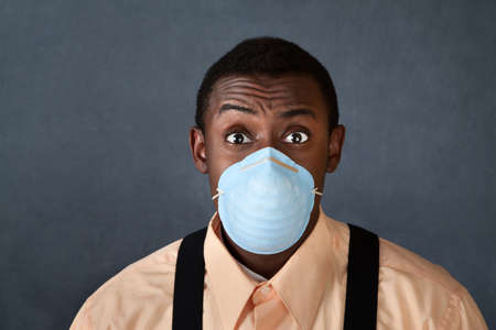Worried young African-American man with surgical mask
