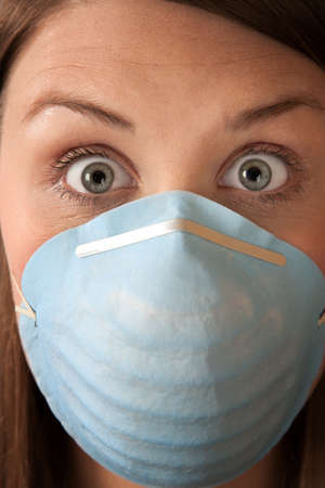 sneeze: Close-up of a scared woman in a surgical mask Stock Photo