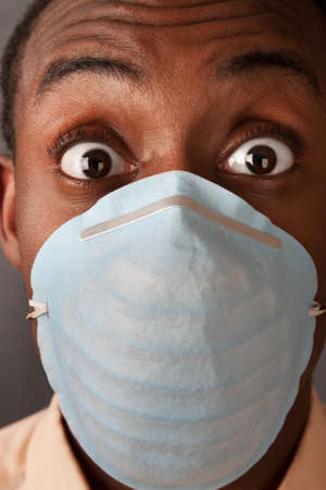 Close-up of a scared man in a surgical mask
