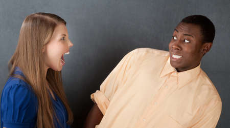 Angry woman in blue dress shouts at attractive African-American male Stock Photo - 9610082