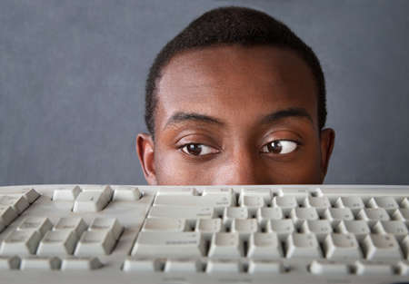 oversee: Young African-American man peeks above a computer keyboard