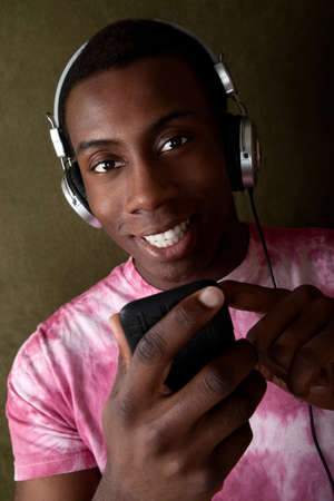 Hansome smiling Black man with headphones selects music on his mp3 player Stock Photo