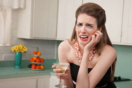 messy kitchen: Caucasian woman with a martini in her kitchen sobs
