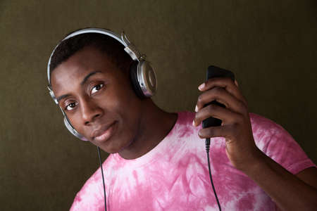 Serious African-American with headphones holds an mp3 player