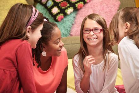 Groep van vier kleine meisjes lachen om een sleepover Stockfoto