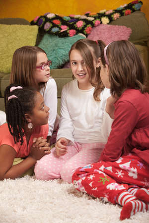 Four chatty little girls in pajamas at a sleepover photo