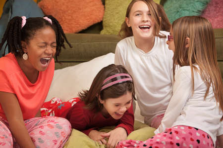 loud: Group of four girls at a sleepover laugh out loud