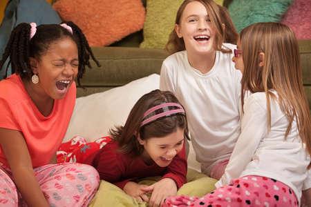 pijamada: Grupo de cuatro ni�as en una carcajada de dormitorio en voz alta