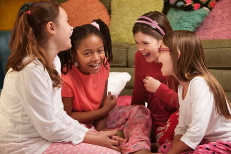 Group of four little girls in pajamas laugh at a sleepover photo