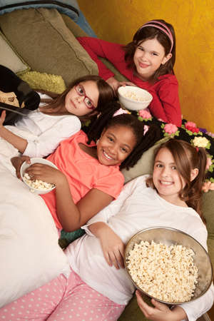 Little girls at a sleepover eat popcorn and tortilla chips  photo