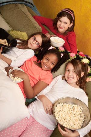pijamada: Ni�as en un dormitorio comen palomitas de ma�z y tortillas fritas