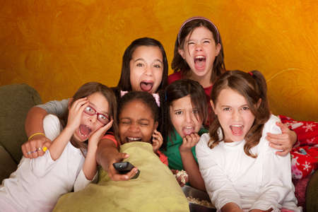 Six girls watching a movie scream at a sleepover photo