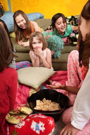 pijamada: Ni�as r�en y comen bocadillos en un dormitorio