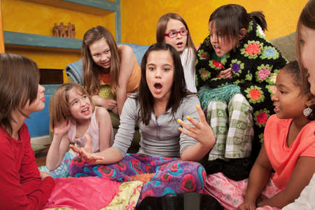 narrate: Excited girl talking with her friends at a sleepover Stock Photo