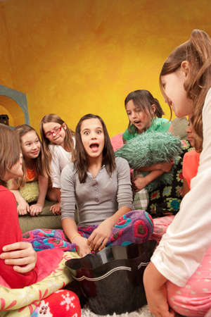 narrate: Teenaged girl tells a story at a sleepover Stock Photo