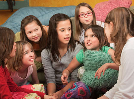 narrator: Little girl tells a story at a sleepover Stock Photo