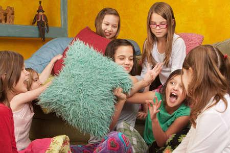 pijamada: Almohada combates entre siete ni�as en un dormitorio Foto de archivo