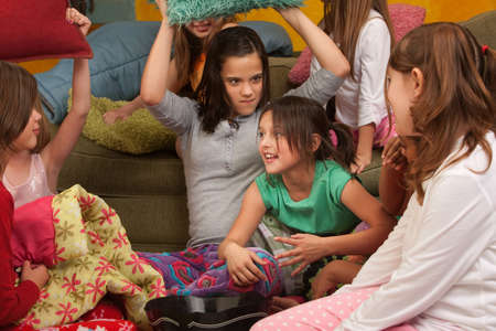 sleepover: Little girl about to get whacked with a pillow at a sleepover