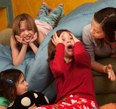 Surprised little girl with hands on head with friends at a sleepover Stock Photo
