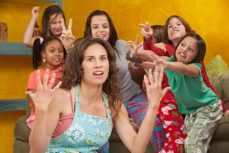 Unhappy mom among wild little girls with hands up in frustration
